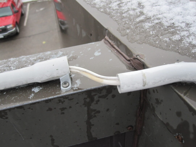 Separated conduit on roof cap requires repair.